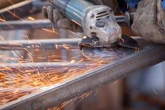 Pracownik używa elektrycznego ostrzarza maszynowego rozcięcia metal błyska obraz stock