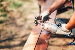 pracownik używa farba pistolet i brown farbę podczas odświeżanie prac Malować ogrodzenie Fotografia Royalty Free