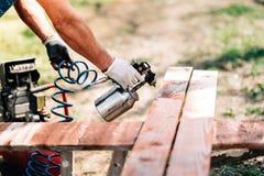 Pracownik używa kiść pistolet dla malować brown szalunek Obrazy Royalty Free