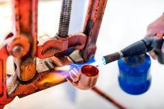 pracownik używa propanu gazu pochodnię dla lutować miedziane drymby Obrazy Royalty Free