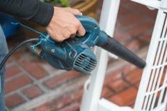 Pracownik używa ręczną dmuchawę usuwać pył Obraz Royalty Free