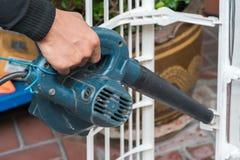Pracownik używa ręczną dmuchawę usuwać pył Obraz Stock