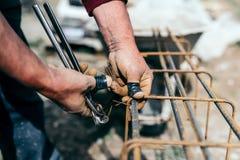 Pracownik używa stalowego drut i chwytniki zabezpieczać stalowych bary, przygotowywa dla betonowego dolewania na przemysłowej bud Zdjęcia Royalty Free