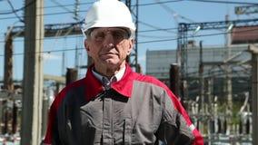 Pracownik w białym ciężkim kapeluszu przy zasilanie elektryczne stacją zbiory
