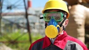 Pracownik w ciężkim kapeluszu, gogle i respiratorze przy elektrownią, zbiory wideo
