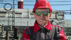 Pracownik w czerwonym ciężkim kapeluszu przy energii jądrowej rośliną zdjęcie wideo
