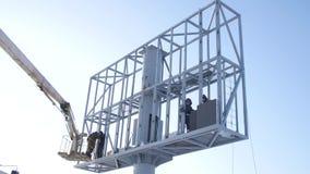 Pracownik w dźwignięcia wiadrze podczas instalacyjnego dużego billboardu w złej pogodzie Pracownicy instalują billboard Pracownic zbiory