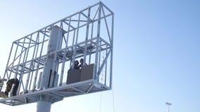 Pracownik w dźwignięcia wiadrze podczas instalacyjnego dużego billboardu w złej pogodzie Pracownicy instalują billboard Pracownic zdjęcie wideo