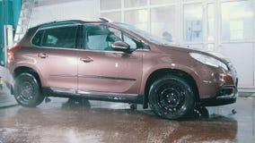 Pracownik w garażu samochodu usługa myje samochód w suds wodnymi wężami elastycznymi, szczegółu zamknięty up zbiory wideo