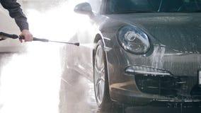 Pracownik w garażu samochodu usługa myje samochód w suds wodnymi wężami elastycznymi zdjęcie wideo