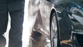 Pracownik w garażu samochodu usługa myje samochód w suds wodnymi wężami elastycznymi - zamyka w górę widoku zbiory