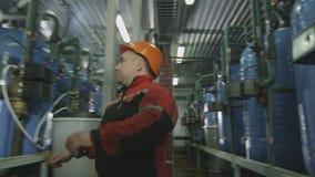 Pracownik w hełmie Kontroluje metry na Benzynowych zbiornikach zbiory