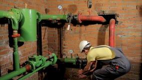 Pracownik w kombinezonach otwiera wodną klapę Mężczyzna zawiera ogrzewanie w kotłowym pokoju zbiory wideo