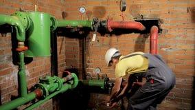 Pracownik w kombinezonach otwiera wodną klapę Mężczyzna zawiera ogrzewanie w kotłowym pokoju zbiory