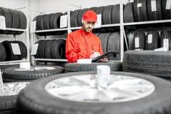 Pracownik w magazynie z samochodowymi oponami obraz stock