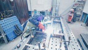 Pracownik w ochronnego kostiumu i maski dyrygentury metalu spawie Fabryczny spawacz zdjęcie wideo