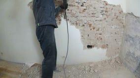 Pracownik w ochronnym kostiumu wyburza tynk ścianę Brudzi, ciężka praca osobiste urządzenia zabezpieczające Hełm, respirator zbiory wideo