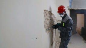 Pracownik w ochronnym kostiumu wyburza tynk ścianę Brudzi, ciężka praca osobiste urządzenia zabezpieczające Hełm, respirator zbiory