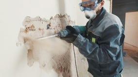 Pracownik w ochronnym kostiumu wyburza tynk ścianę Brudzi, ciężka praca osobiste urządzenia zabezpieczające Hełm, respirator zdjęcie wideo