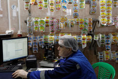 Pracownik w przylepiać etykietkę warsztat karmowy zakład przetwórczy obraz stock