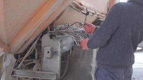 Pracownik w przypadkowych ubraniach stawia dalej śmietnika używać grat maszynę Tylny widok mężczyzna kontroluje śmieciarską maszy zbiory