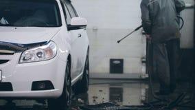Pracownik w samochód usługa myje samochód w suds wodnymi wężami elastycznymi zbiory