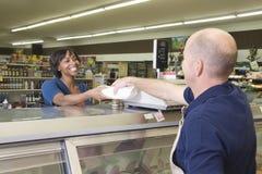 Pracownik Wręcza produkt klient W supermarkecie Fotografia Royalty Free