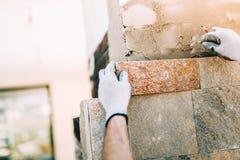 pracownik z kamień płytkami w budowie kamieniarstwo szczegóły instaluje sto na zewnętrznej ścianie z kielnią kitują knifeworker zdjęcia royalty free