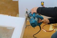 Pracownik z kurendą zobaczył maszynę przy ciąć drewnianego drzwi zdjęcie royalty free