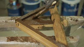 Pracownik z muśnięciem maluje drewnianą część meble lub produkt zbiory