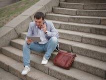 Pracownik z pastylką i opowiadać na telefonie, siedzi na miastowym tle Technologia postępu pojęcie kosmos kopii Obrazy Stock
