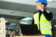 Pracownik z przeszukiwaczem i laptopem przy spedycją zdjęcia stock