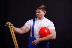 Pracownik z spirytusowym poziomem w jego ręce trzyma je pionowo na czarnym tle Obrazy Royalty Free