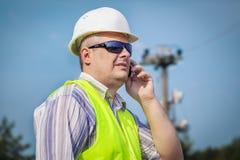 Pracownik z telefonem komórkowym na niebieskiego nieba tle obraz royalty free