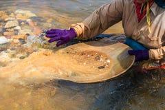 Pracownik zbiera kopalinę przy rzeką Zdjęcia Stock