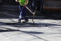 Pracownik zrównuje kruszkę asfalt w jamie z rolownikiem przed brukowaniem z drogowym mini budynku rolownikiem Zdjęcia Stock