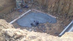 Pracownika budowlanego gipsowanie wokoło centrum palowej podstawy przed use żaluzi deskami i dolewanie betonem dla centrum filaru zbiory wideo