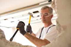 Pracownika budowlanego mienia narzędzie i roztrzaskania drywall Fotografia Stock