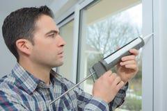 Pracownika budowlanego pieczęciowy okno w domu zdjęcia stock