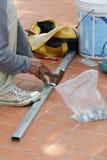 Pracownika budowlanego ` s wręcza działanie na aluminium ramie z młotem Fotografia Royalty Free