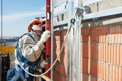 Pracownika budowniczy przy fasadowymi robotami budowlanymi Zdjęcie Stock