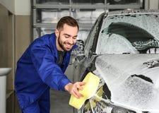 Pracownika cleaning samoch?d z g?bk? przy samochodowym obmyciem obraz stock