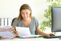 Pracownika czytania raporty przy biurem Obraz Stock
