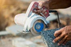 Pracownika granitu tnący kamień z diamentowy elektrycznym zobaczył ostrze i używa wodę zapobiegać pył i ogrzewać zdjęcie stock