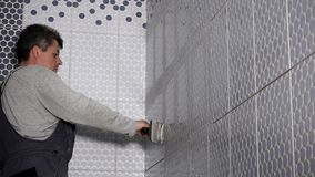 Pracownika kładzenia fuga na ścianie tafluje złącza w łazience Mężczyzna grouting płytki zbiory wideo