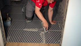 Pracownika kładzenia fuga na podłodze w łazience ceramiczne płytki zbiory
