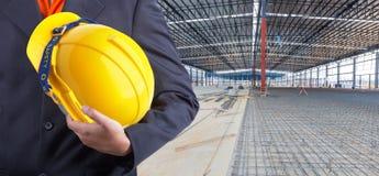 Pracownika lub inżyniera mienie w ręka koloru żółtego hełmie Obrazy Stock