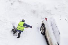 Pracownika mężczyzna przeszuflowywa śnieżnego pobliskiego samochód na parking Odgórny widok śnieżna odprawa obrazy stock