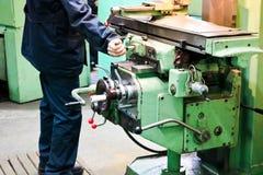 Pracownika męskie pracy na wielkim metalu odprasowywają locksmith tokarkę, wyposażenie dla napraw, metal praca w warsztacie przy  zdjęcia stock