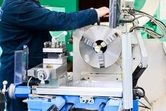 Pracownika męskie pracy na wielkim metalu odprasowywają locksmith tokarkę, wyposażenie dla napraw, metal praca w warsztacie przy  obraz royalty free